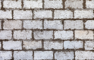Old weathered white brick wall as background