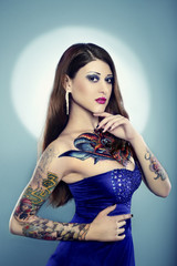 Portrait of beautiful woman with tattoo in blue dress