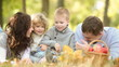 Happy family playing outdoors in autumn park