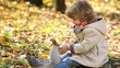 Happy child feeds a little squirrel in autumn park
