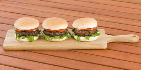 Hamburgers - Burgers in white buns with summer leaf and tomato.