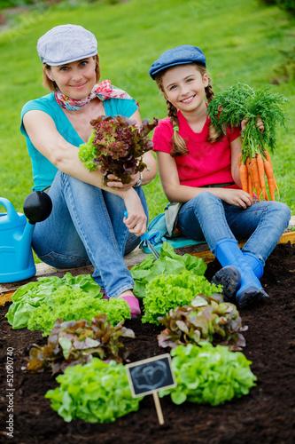 Gardening, vegetable - girl helping mother in the garden
