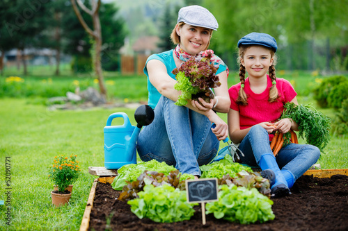 Gardening - mother and daughter working in vegetable garden