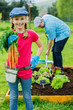Gardening, planting - girl helping father in the garden