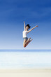 Asian girl jump at white sand beach