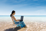 Attractive woman typing on laptop at beach
