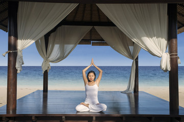 Attractive woman practice yoga at luxury beach resort