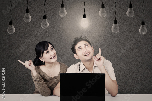 Couple with laptop looking at lit bulb
