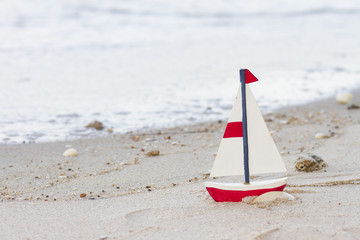 wooden boat, red wooden mini sailboat on sand beach