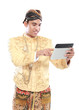 man with traditional java suit using tablet PC