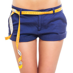 Closeup of fit female hips in blue shorts with measuring tape
