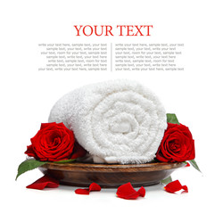 Rolled white towel and roses and rose petals