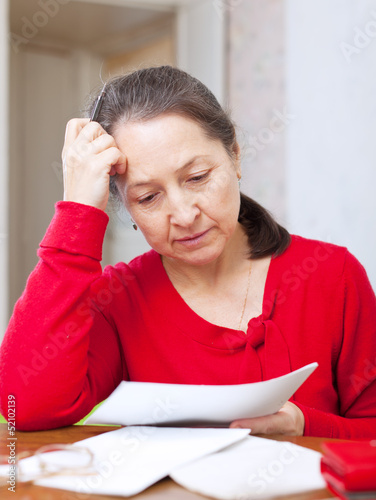 Sadness mature woman with bills