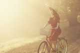 Girl on a bike in the countryside in sunrise time