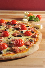Pepperoni pizza with fresh cherry tomatoes and olives