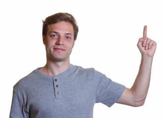 Junger Mann in Jeans und Shirt zeigt nach oben