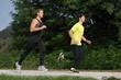 Two Men Athletes Running Through Park