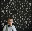 Boy businessman with chalk questions blackboard