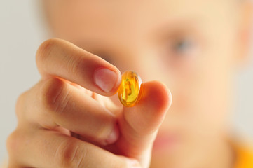Close up of kid holding yellow pill