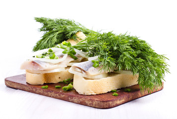 Sandwiches with herring, onions and herbs on white background