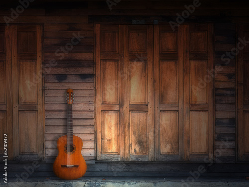 old classic guitar on wood wall