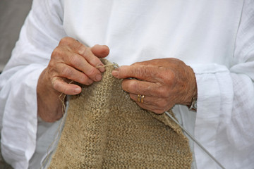 hands of an elderly woman during the processing of wool sweater