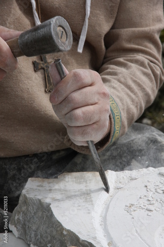 stonemason with ancient costume during the processing of the sto
