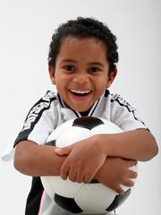 Dunkelhäutiger Junge mit Ball und Trikot im Deutschland-Look