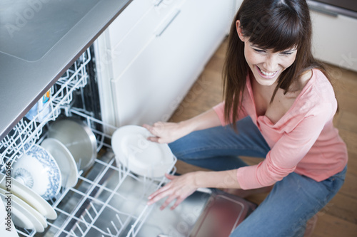 middle aged girl in the kitchen using diswasher