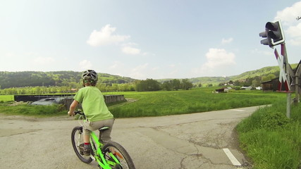 Kind fährt mit dem Fahrrad üner einen Bahnübergang