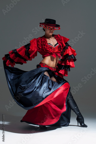 Woman in beautifull red dress dancing in a studio