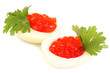 Red caviar in eggs isolated on white