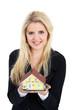 Junge Frau überreicht freundlich lächelnd ein Haus