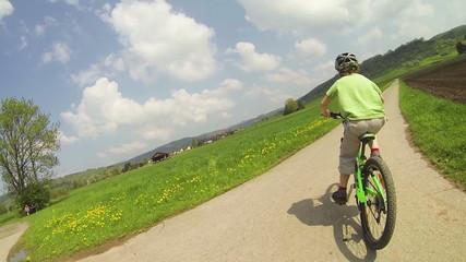 Kind fährt Rechtskurve mit dem Fahrrad