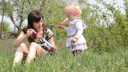 Mother with baby blows soap bubbles. Dolly shoot.