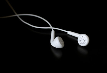 White earphones on black reflective surface