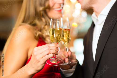 Man and woman tasting Champagne in restaurant - 52121190