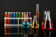 Test tubes with colorful liquids on dark grey background
