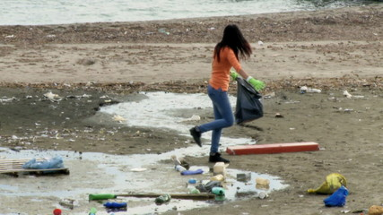 Young social worker cleaning dirti beach