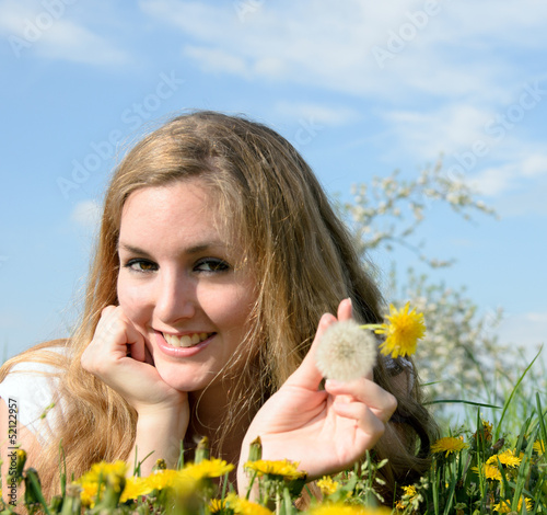 Young woman relaxing between dandelions