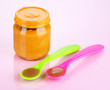 Baby food with weaning spoons on purple background