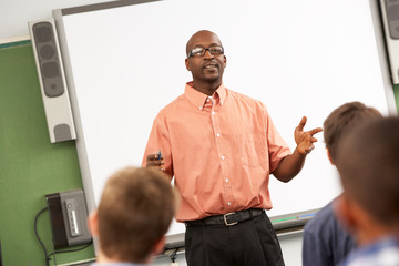 Teacher Talking To Class Standing In Front Of Whiteboard