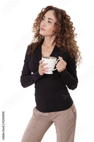 Woman with thick hair stands holding a coffee cup.