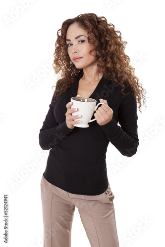 Woman in tan pants and a black shirt holds a coffee cup.