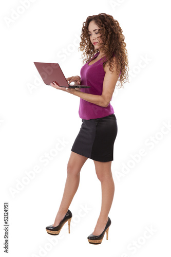 Woman in black skirt uses her computer while standing.