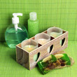 Candles in wooden candlestick, cosmetics bottles and soap,