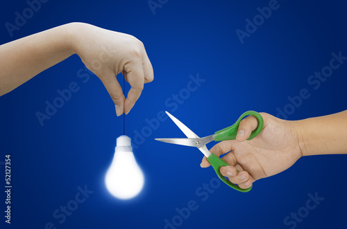 hand holding light bulb and scissors