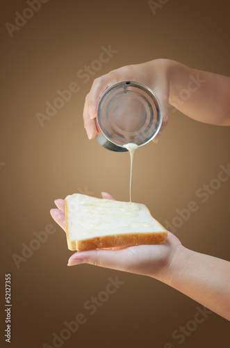 hand holding condensed milk can with bread