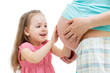 kid girl touches pregnant mother's belly isolated
