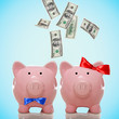 Hundred Dollar bills falling in a piggy bank couple